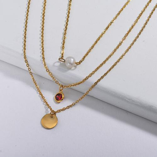 Dije redondo dorado simple con collar multicapa de perlas y piedra natal roja