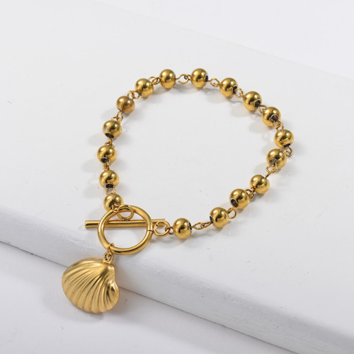 pulsera de bola de acero inoxidable de color dorado y colgante de concha