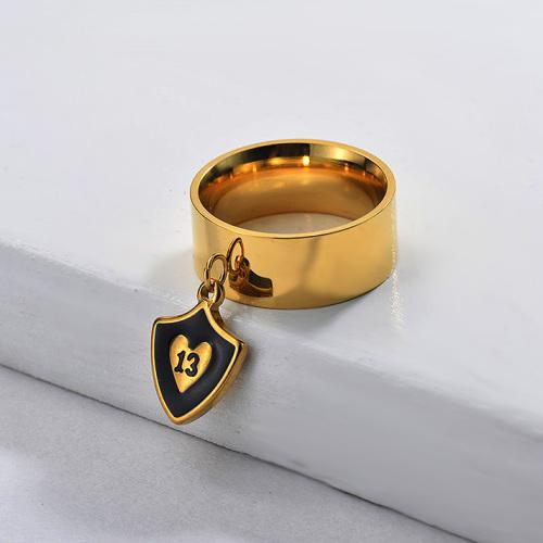 Anillo ancho con dije de escudo de esmalte negro y chapado en oro