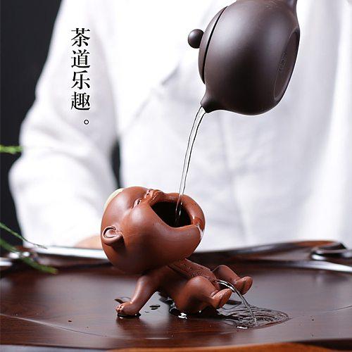 The ceramic tea pet laughs with the purple sand child